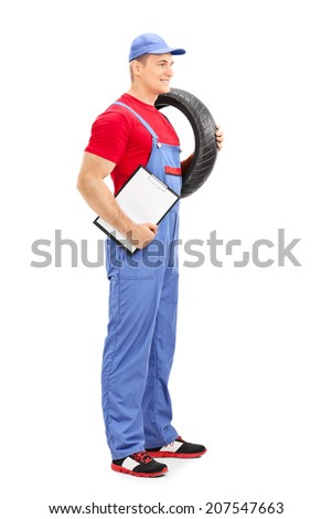 Profile shot of a male mechanic holding a tire and a clipboard isolated on white background - stock photo