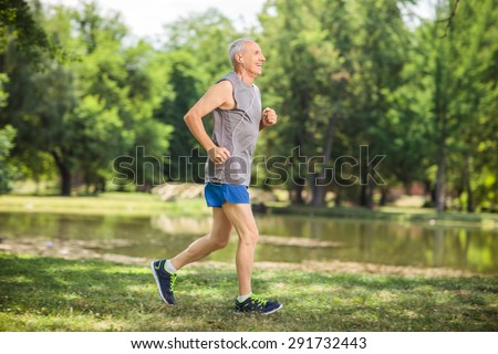 Profile shot of an active senior jogging in a park and listening to music on headphones - stock photo