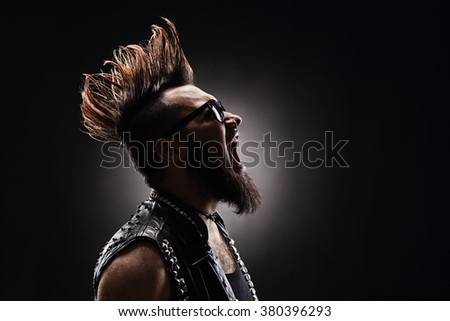 Profile shot of an angry punk rocker shouting on dark background - stock photo