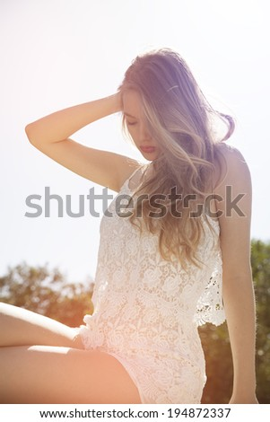 profile shot of beautiful exotic blonde with long blond curly hair. vertical shot in summer outfits. Toned in a warm colors.Backlight - stock photo