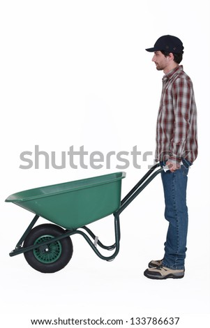 Profile shot of man stood with wheelbarrow - stock photo