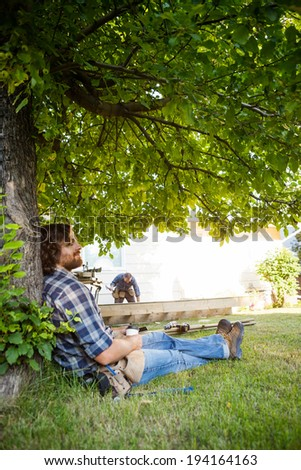 Profile shot of manual worker with eyes closed leaning on tree trunk while coworker working in background - stock photo