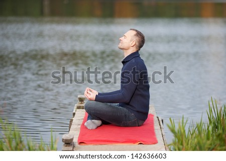 Profile shot of mature man meditating in lotus position on pier against lake - stock photo