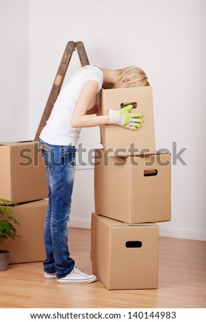 Profile shot of young woman searching something in cardboard box - stock photo