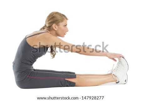 Profile shot of young woman stretching to touch her toes while sitting against white background - stock photo