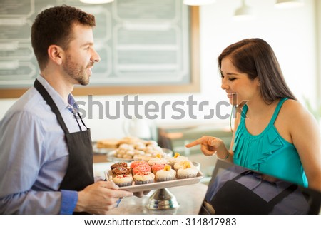 Profile view of a cute female customer pointing at a cupcake she wants to buy in a cake shop. Focus on woman - stock photo