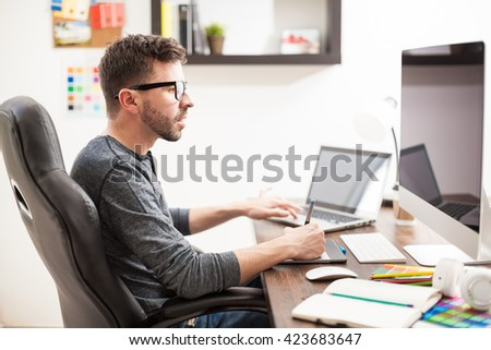 Profile view of a good looking Hispanic young man multitasking at work, using two computers at once - stock photo