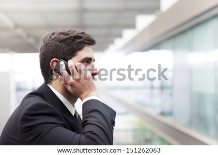 Profile view of a handsome young business man talking on cell phone - stock photo