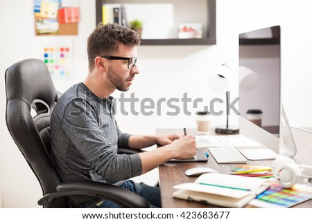 Profile view of a handsome young male graphic designer working in front of a computer in a trendy workspace - stock photo