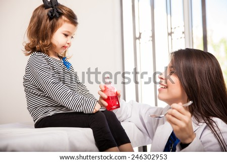 Profile view of a little girl who was just given some cough syrup by her pediatrician - stock photo
