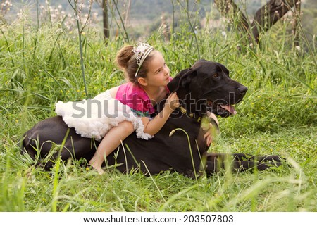 Profile view of a pretty young girl wearing a pink fancy dress, sitting on her dogs back enjoying a sunny holiday in a green park field, hugging him outdoors. Active family with pets, lifestyle. - stock photo