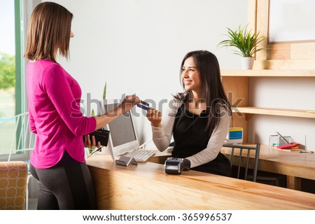 Profile view of a pretty young woman paying with a credit card at a store - stock photo