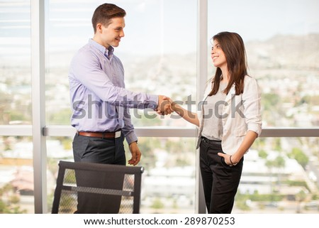 Profile view of a young handsome man giving a woman a handshake in a meeting room - stock photo