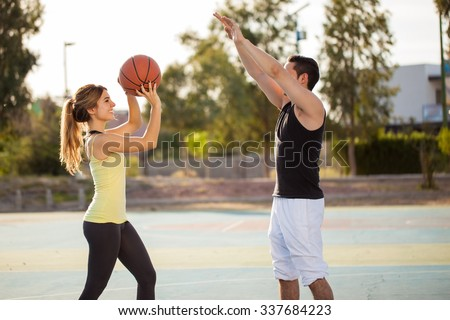 Profile view of a young man and his girlfriend playing basketball against each other on an outdoor court - stock photo