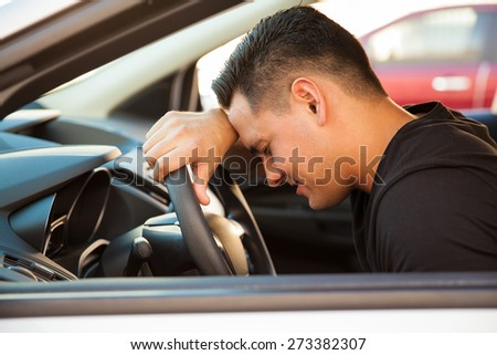 Profile view of a young man leaning on the steering wheel and feeling stressed and upset - stock photo