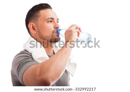 Profile view of a young man with a beard drinking water from a bottle after working out - stock photo