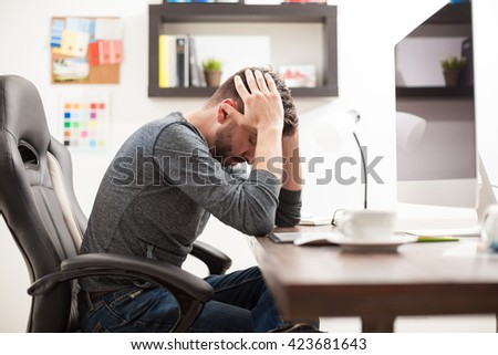 Profile view of a young man with a headache feeling unwell while sitting in front of a computer at the office - stock photo