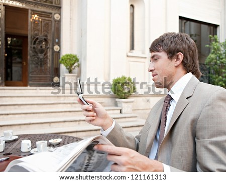 Profile view of an attractive businessman using a cell phone while reading the newspaper in a coffee shop terrace with classic office buildings in the background, smiling. - stock photo
