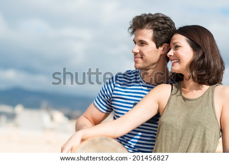 Profile view of an attractive young couple sitting close together on a sandy beach looking out towards the ocean, with copyspace - stock photo