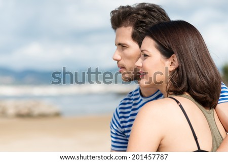 Profile view of an attractive young couple standing on a sandy tropical looking out over the sea, with copyspace - stock photo