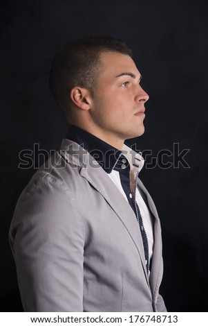 Profile view of elegant handsome young man with shirt and jacket, dark background - stock photo