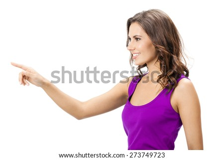 Profile view of happy smiling beautiful young woman in casual smart lilac clothing, showing copyspace, visual imaginary or something, or pressing virual button, isolated against white background - stock photo