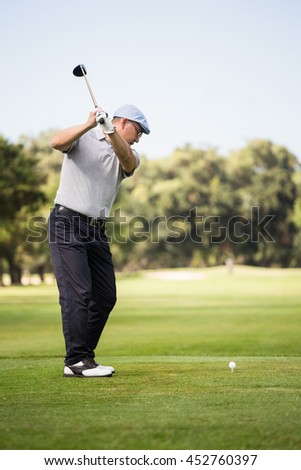 Profile view of man playing golf while standing on field - stock photo