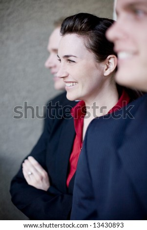 profile view of three businesspeople standing in line wearing formal clothing smiling - stock photo