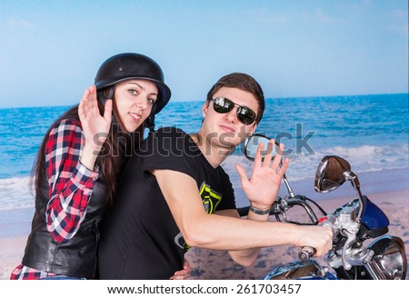 Profile View of Young Couple on Motorcycle at Beach Waving to Camera - stock photo