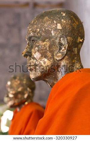 Profile view on a Buddha statue covered with golden leaves in the Wat Chalong Buddhist temple in Chalong, Phuket, Thailand - stock photo