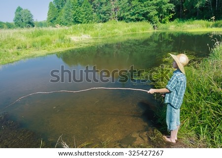 Profile view portrait of barefoot fisher boy in transparent brownish waterbody  - stock photo