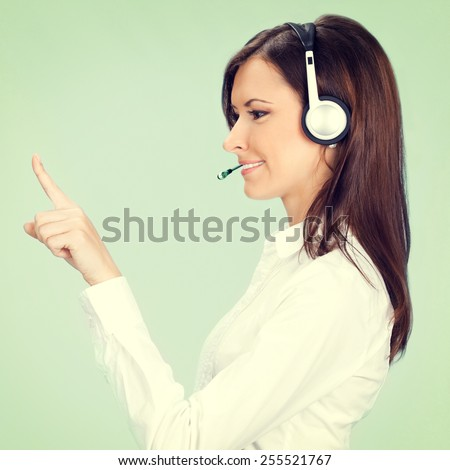 Profile view portrait of happy smiling cheerful customer support phone operator in headset pointing at something, on green background - stock photo