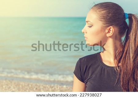 profile Young woman on background of sea enjoying the sun - stock photo