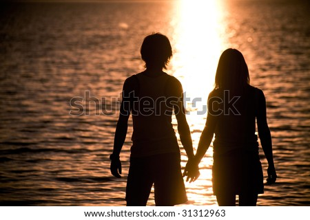 Profiles of romantic couple holding each other by hands and admiring lake at sunset - stock photo
