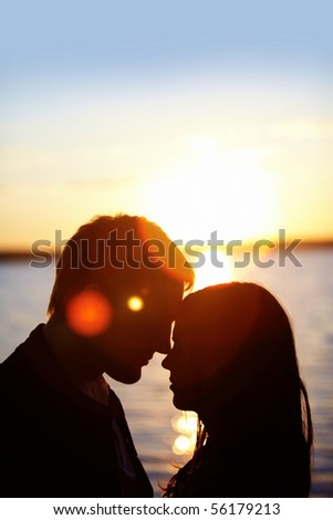 Profiles of romantic couple looking at each other on background of sunset - stock photo