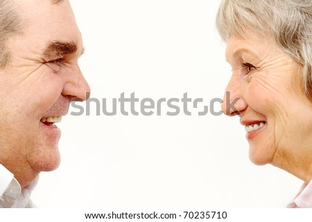 Profiles of senior woman and man face to face - stock photo