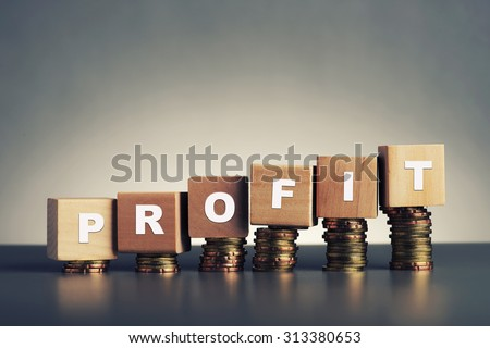 profit text written on wooden block with stacked coins on grey background - stock photo