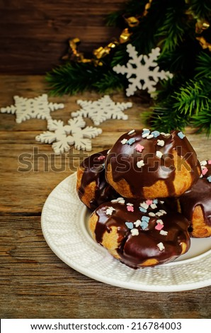 profiteroles with chocolate icing and colored powder on a dark wood background. tinting. selective focus on the middle of top profiterole - stock photo