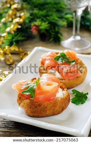 profiteroles with salmon and cream cheese on a dark wood background. tinting. selective focus on parsley on the front profiterole - stock photo