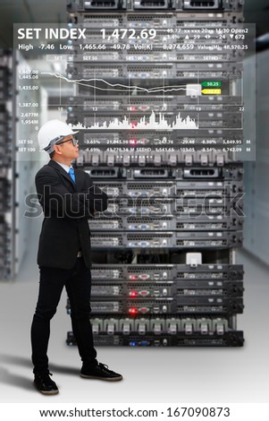 Programmer in data center room and graph report - stock photo