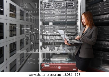 Programmer in data center room working with laptop - stock photo