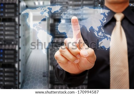 Programmer touch on world map control in data center room - stock photo
