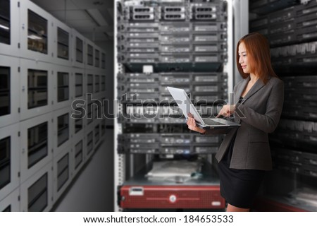 Programmer working with laptop in server room  - stock photo