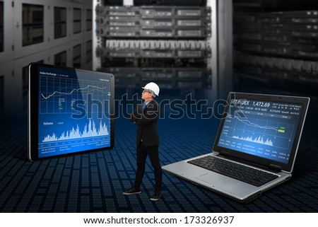Programmers in data center room working with laptop and tablet - stock photo