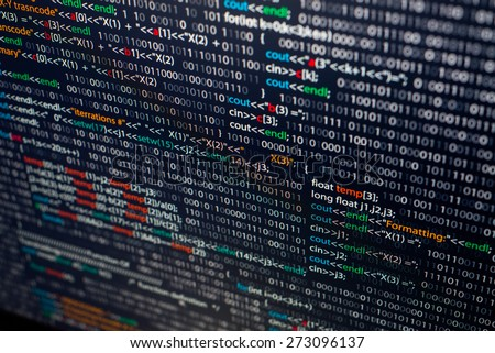 Programming abstract - source code and binary code on display of software developer. Black theme with colored syntax.  - stock photo