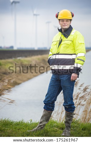 Project developer stands confident in a green landscape with his reflective jacket and safety helmet - stock photo