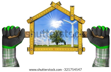 Project of an Ecological House / Hands with work gloves holding a wooden meter ruler in the shape of house with wind turbines in countryside with tree, blue sky, clouds and sun rays. - stock photo