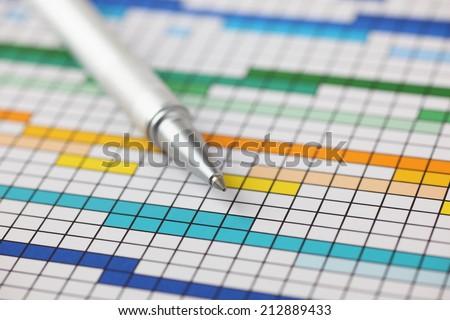 Project Plan (Gantt chart) and ballpoint pen on it. Close-up. - stock photo