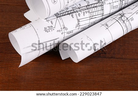Projects of houses on the wooden background - stock photo