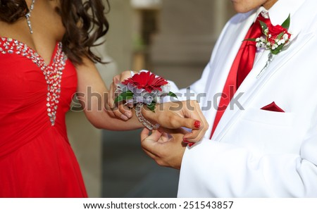 Prom Couple - a close up of the boy giving his date a red floral wrist corsage  - stock photo
